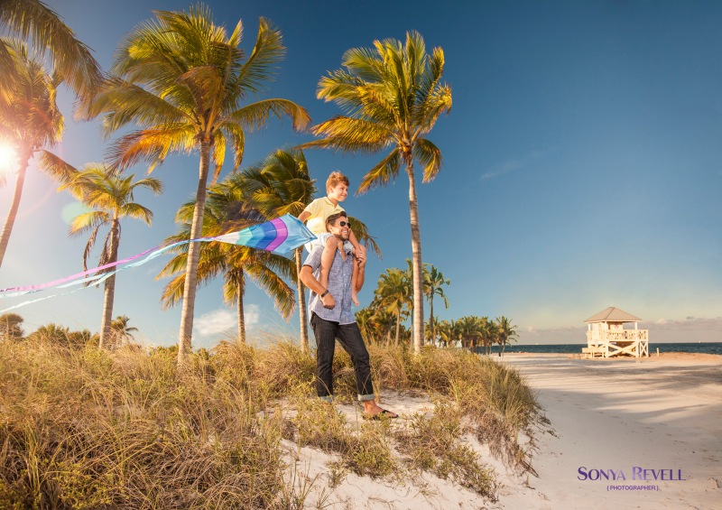 lifestyle photography of father and son flying kite at beach on sunny day