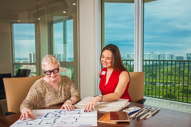lifestyle-photography-of-senior-woman-looking-over-floor-plans-with-younger-assistant