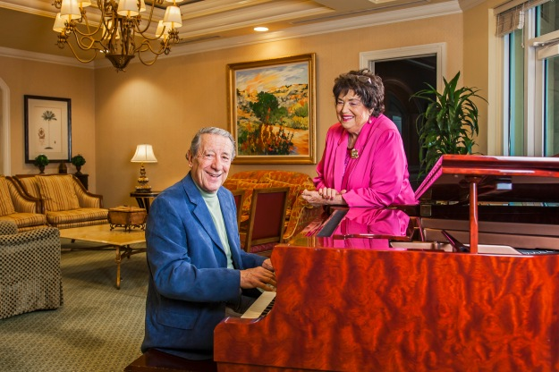 portrait-photography-of-senior-man-playing-piano-while-senior-woman-looks-on