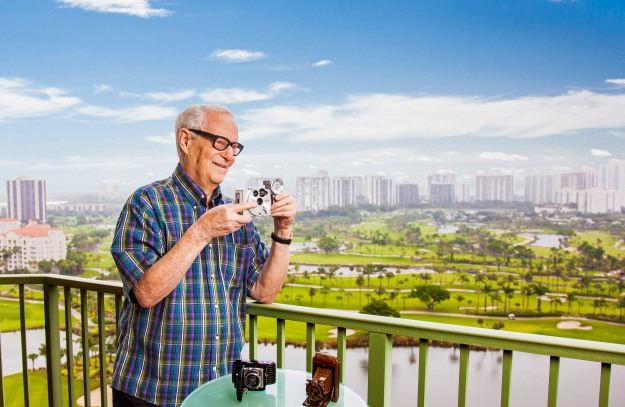portrait-photography-of-senior-man-with-vintage-camera-on-balcony-overlooking-aventura-florida
