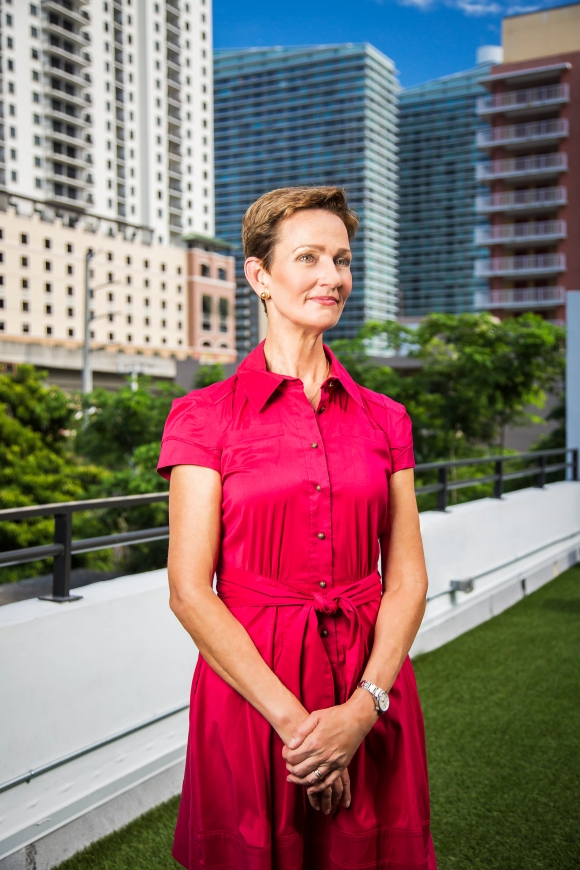 portrait photography of meg daly in pink dress standing on rooftop in front of brickell skyline