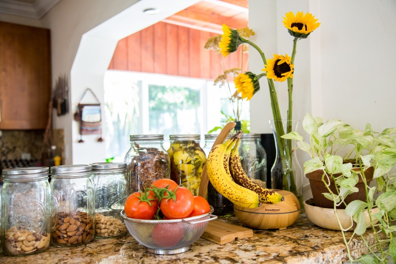 photograph-of-kitchen-counter-lined-with mason-jars-and-fresh-fruit