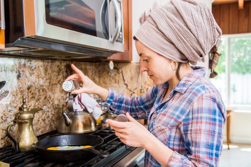 photo of Batsheva cooking eggs in her kitchen