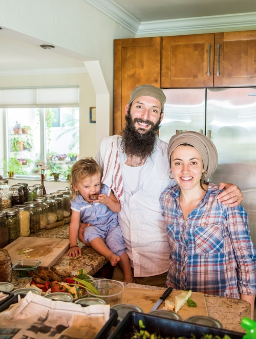 portrait photo of zak and batsheva with their daughter in the kitchen