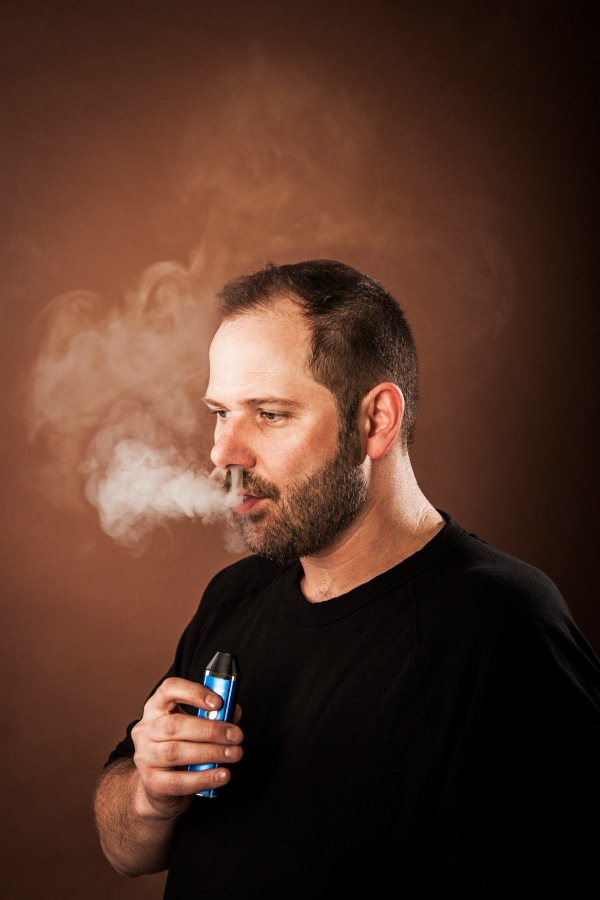 portrait photography of Jan Verleur blowing smoke holding e-cigarette