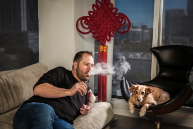 portrait photography of Jan Verleur vaping on a sofa with his dog nearby