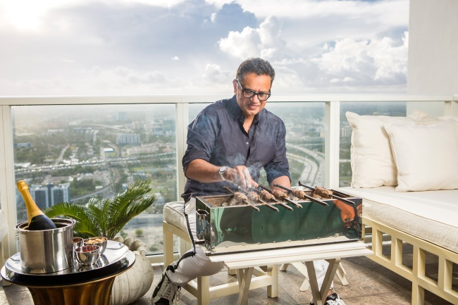 portrait photography of naeem khan cooking kebabs over a japenese grill