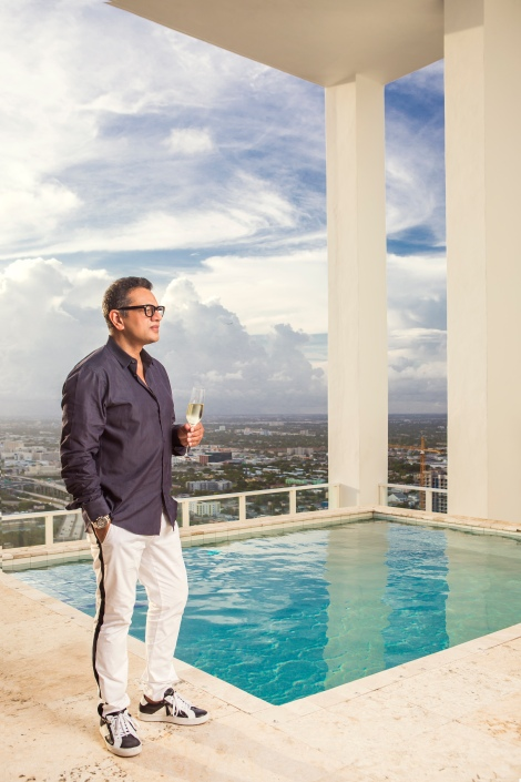 portrait photography of naeem khan standing on a pool deck high above miami