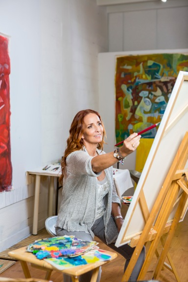 portrait photography of artist Isabel Brinck painting in her studio