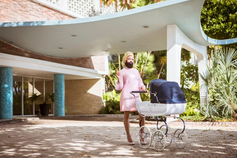 photo of a drag queen with a baby pram stroller in front of 1960s building