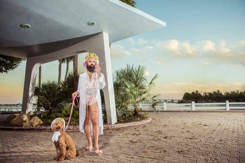 photo of a drag queen with curlers walking a dog with curlers and smoking a cigarette