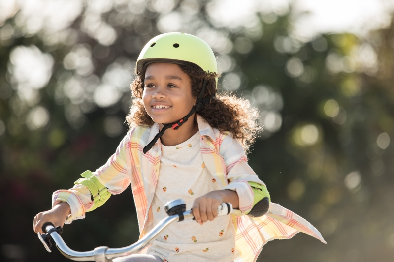 photo of a young girl riding a bike wearing a helmet