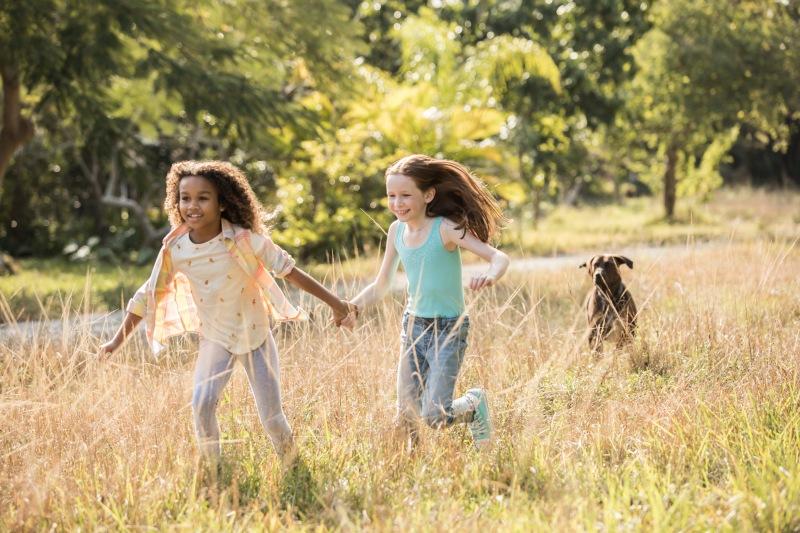 Photo of Girls running through field holding hands