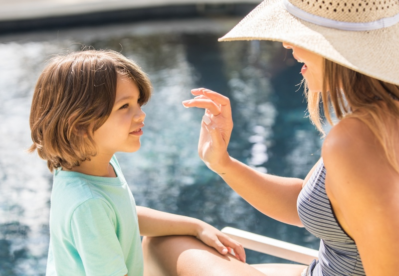 photo of a woman applying sunscreen to a little boy next to a pool