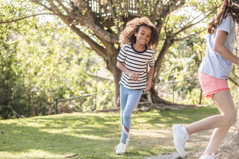 photo of two girls playing chase outside in a backyard