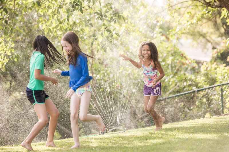photo of young girls playing in a backyard sprinkler