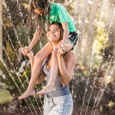 photo of a woman with a little girl on her shoulders, playing in a backyard sprinkler