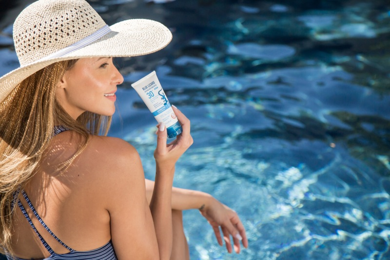 photo of a female model holding blue lizard sunscreen next to a pool