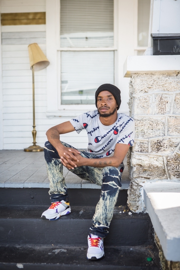 portrait photography of Hakeem Drane, sitting outside on steps