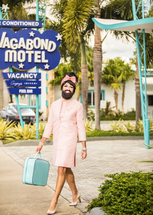 conceptual portrait photography of bearded drag queen wearing a pink 1960s era dress outside the Vagabond hotel in Miami